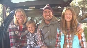 famiglia che si siede nel bagagliaio aperto della macchina, vicino colpo palmare video
