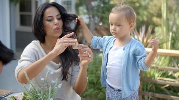 madre a casa con la figlia che mangia pasto in giardino video