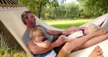 papà moderno abbraccia il suo bambino biondo sull'amaca in giardino