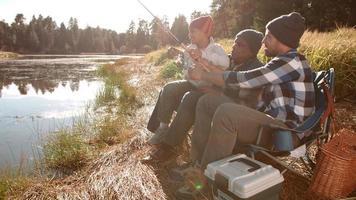 il nonno e il padre si siedono insegnando al ragazzo a pescare in un lago video