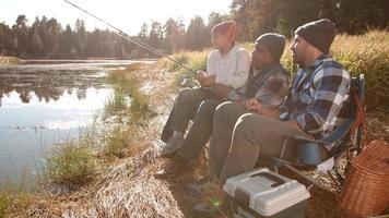 avô e pai sentados mostrando ao menino como pescar perto de um lago video