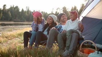 genitori e due bambini siedono a parlare fuori dalla tenda video