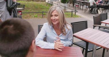 Mujer madura tomando un café al aire libre con su hijo video