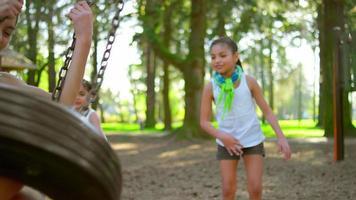 ragazze che spingono vicenda su un'altalena di pneumatico in un parco