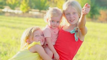 süße blonde Mädchen draußen mit einem Kleinkind