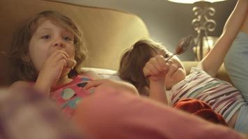 garotinhas no sofá assistindo televisão e comendo donuts e manteiga de amendoim