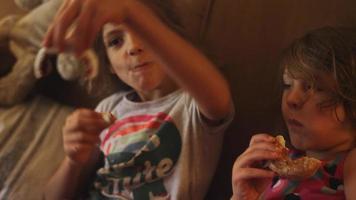 uma garotinha coloca um donut no rosto da irmã e deixa geléia em seu nariz