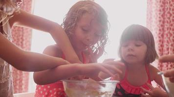 três meninas comendo massa de biscoito em uma tigela