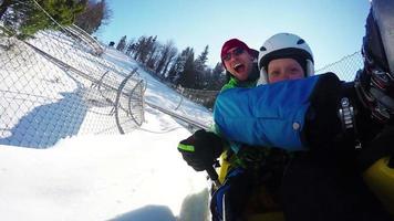 Images 4k du père et du fils en train de profiter de l'attraction de bobsleigh d'hiver