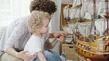Curious Toddler Boy Looking at Ship Model video