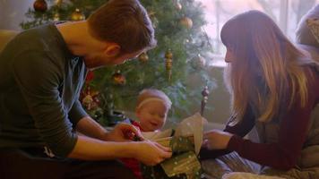 parents ouvrant des cadeaux avec leur bébé devant l'arbre le matin de Noël
