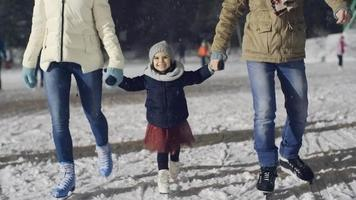 cutie patinando sobre hielo con los padres
