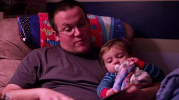 A father reads a book to his little boy in a rocking chair before bed video