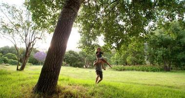 moderner Vater spielt mit Sohn auf Schaukel im Park