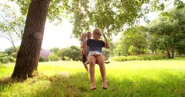 moderner Vater spielt mit Söhnen auf Schaukel im Park