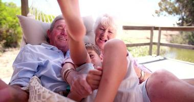 abuelos riendo mientras le hacen cosquillas a su nieto