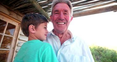 nonno e nipote sorridendo e abbracciando all'aperto