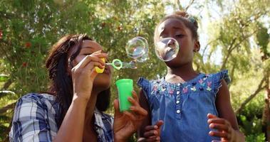 mulher fazendo bolhas de sabão com a filha dele