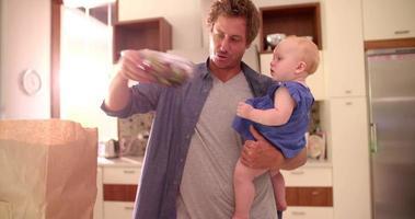 Papá moderno desembalaje de comestibles con niña en brazos