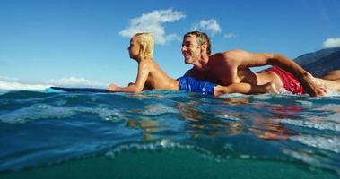 padre e sole che fanno surf