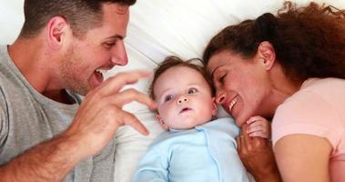 neonato in babygro blu con genitori felici sul letto