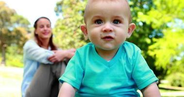 lachender kleiner Junge, der mit Mutter auf dem Gras sitzt