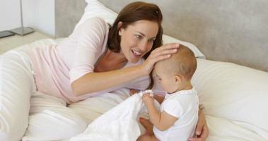 madre che gioca con la sua bambina sul letto