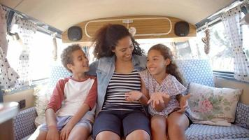 Smiling mum and kids travelling in the back of a camper van