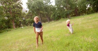 ragazzi che si divertono a correre dietro le bolle che volano nel parco