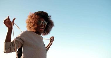 Amante de la diversión hipster adolescente afroamericano en la playa riendo