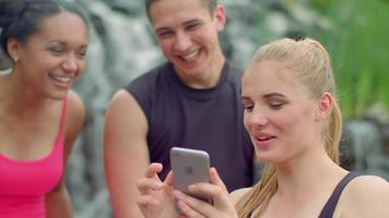 Happy people laughing. Friends having fun with phone outdoor
