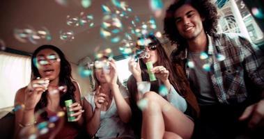 Amigos hipster divirtiéndose con burbujas dentro de una camioneta vintage