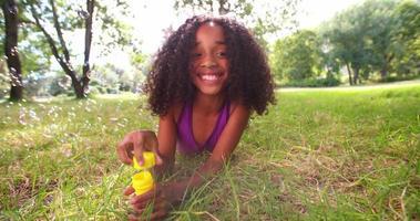 divertente ragazza afro che soffia bolle in un parco al rallentatore