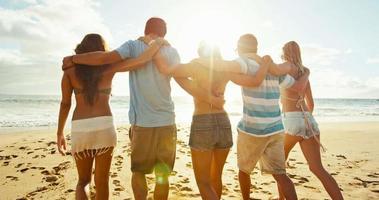 grupo de amigos se divertindo caminhando na praia ao pôr do sol