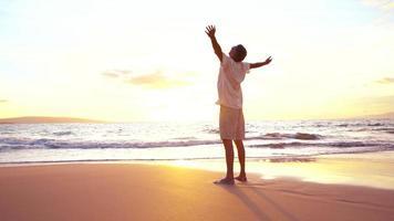Freiheit am Strand. reifer pensionierter Mann, der Spaß am Sonnenuntergang hat