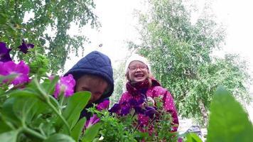 blonder Junge und Mädchen mit Brille schnüffelt Blumen. Kinder haben Spaß und lachen.