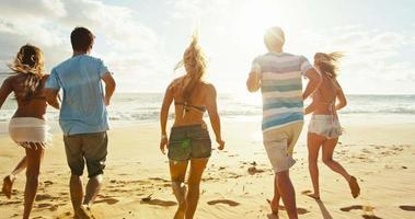 gruppo di amici che hanno divertimento passeggiando per la spiaggia al tramonto video