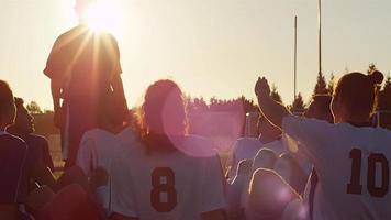 A soccer team sitting in a circle playing a fun game at sunset
