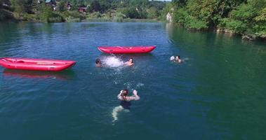 junge Freunde, die Spaß daran haben, im Fluss zu schwimmen und sich gegenseitig mit Wasser zu bespritzen