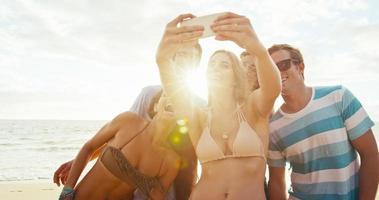 felice gruppo di amici divertendosi a scattare una foto insieme sulla spiaggia video