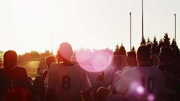 un equipo de fútbol sentado en un círculo jugando un juego divertido al atardecer