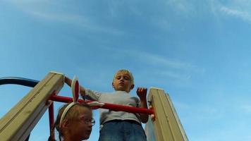 ragazza con orecchie e occhiali e ragazzo con i capelli bianchi divertirsi sulla torre dei bambini.