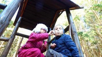 chico rubio y chica con gafas hacen burbujas en el patio de recreo. los niños son muy divertidos. se divierten y ríen. video
