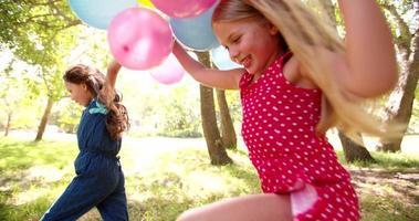 Niños felices y amigables divirtiéndose con globos al aire libre