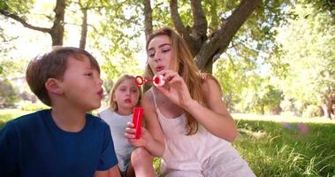 niño con mamá y hermana divirtiéndose con burbujas