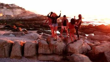 Hipster fun loving friends dancing at beach on sunset
