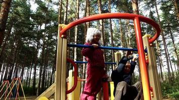 niño y niña divirtiéndose en el tobogán infantil en el parque. los niños se ríen y se complacen. domingo feriado con niños en el parque.