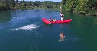junge Freunde, die Spaß haben, vom Kanu in den Fluss zu springen