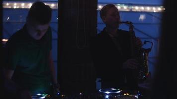 DJ girando na plataforma giratória. homem tocar saxofone. festa na boate. silhuetas