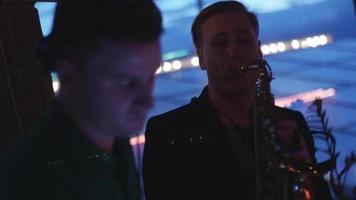 DJ girando na plataforma giratória. homem tocar saxofone. festa na boate. músicos